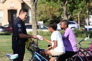 Sacramento Police Officer hands an item to two kids on bikes