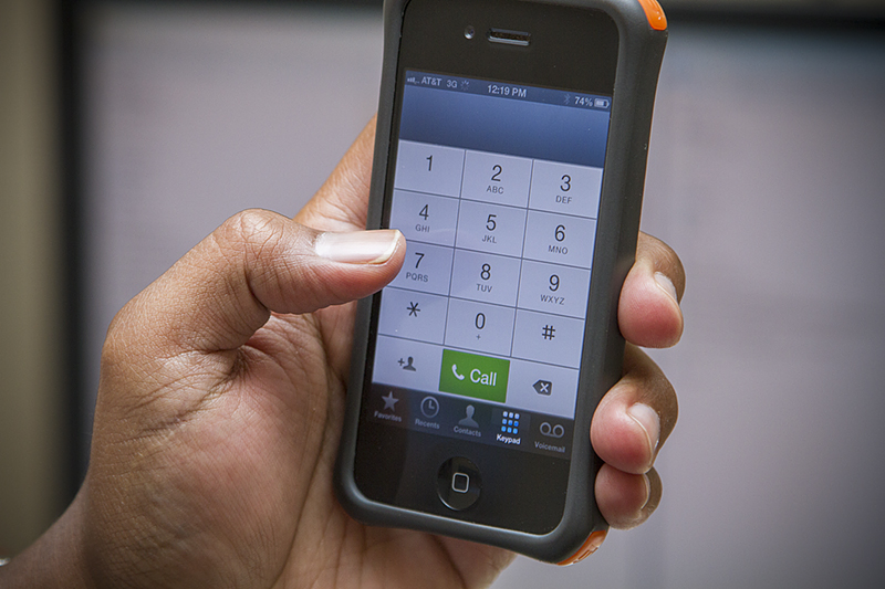 Hand holding a mobile phone - Dial 311 for assistance