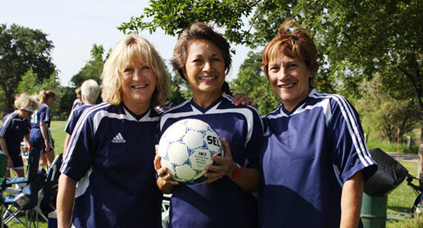 Three women soccer players smiling at camera