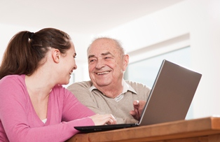 Younger adult female and older adult male using laptop