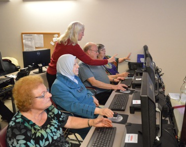Instructor assists older adult students during a computer class