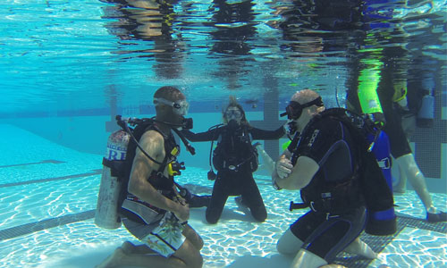 Participants receiving scuba diving instruction in pool