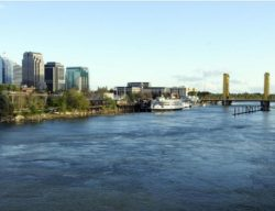 This image shows the I Street Bridge and the river below with a few downtown buildings on the right side of the photo.