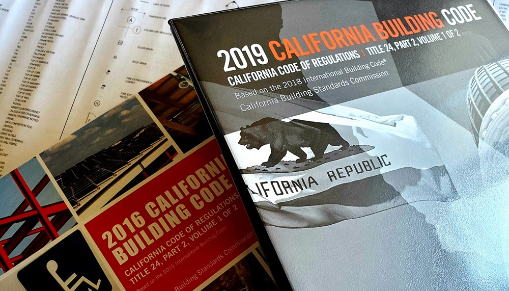 Image of the 2016 and 2019 California Building Code with contstruction plans in the background.