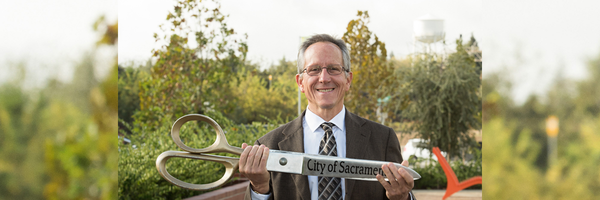 "Sacramento City Council District 3 Councilmember Jeff Harris holds large scissors labeled ""City of Sacramento."""
