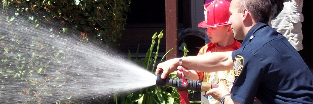Firefighter and boy spraying water from hose