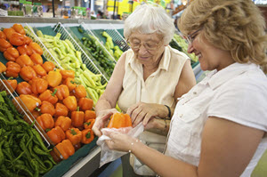 Younger female assists older female with groceries