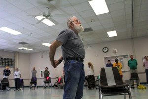 older man leads strength and balance class