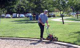 Park Maintenance Employee edging park lawn
