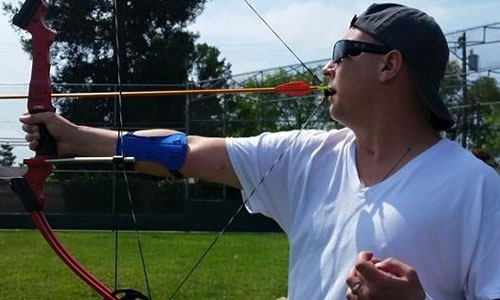 Participant in archery using mouth tab on bow to shoot arrow