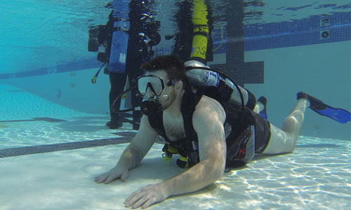 Participant receiving scuba diving instruction in pool