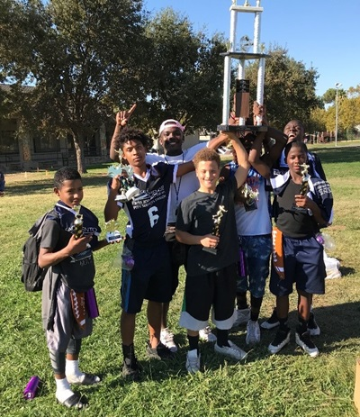 Kid's in flag football jersey's holding up trophy