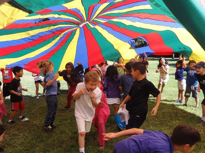 kids playing under colorful tarp