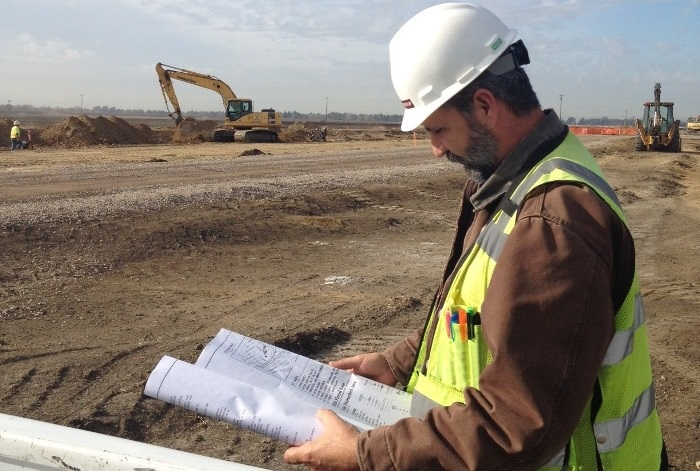 Construction Inspector reviewing documents at a construction site