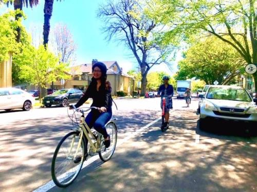 Two women riding a bike and a Jump scooter