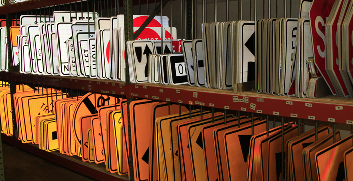 Traffic signs arranged on shelves in the signs and markings shop